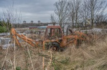 Abandoned tractor being reclaimed by nature, with the Tyneside skyline in the background.